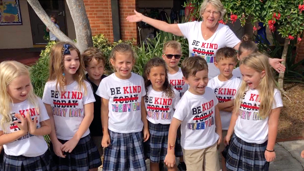 Teacher poses with first grade students in their kindess t-shirts.